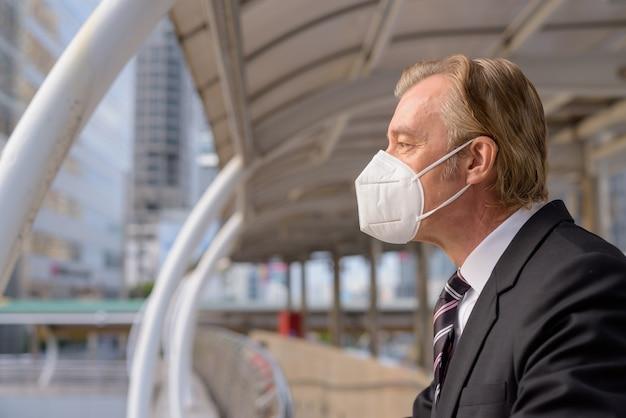 歩道橋から街の景色を見てマスクを持つ成熟した実業家の縦断ビュー