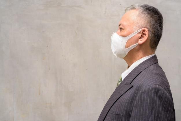 屋外のマスクを持つ成熟した日本のビジネスマンの縦断ビュー