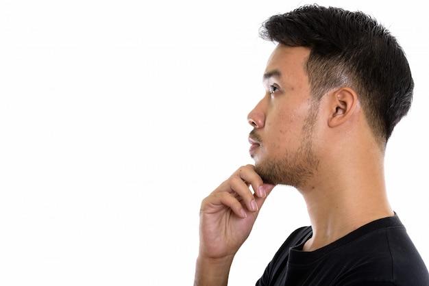 Взгляд профиля молодого азиатского человека думая пока смотрящ вверх