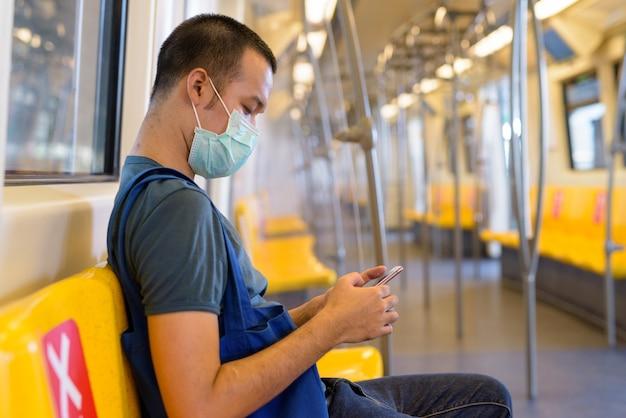 Вид профиля молодого азиатского человека с маской, использующего телефон и сидящего на расстоянии внутри поезда