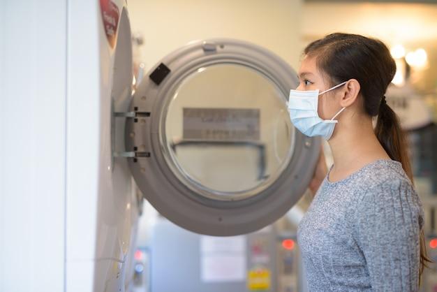 Вид профиля молодой азиатской женщины с маской, смотрящей внутрь стиральной машины в прачечной самообслуживания