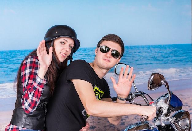 カメラに手を振ってビーチでオートバイの若いカップルの縦断ビュー