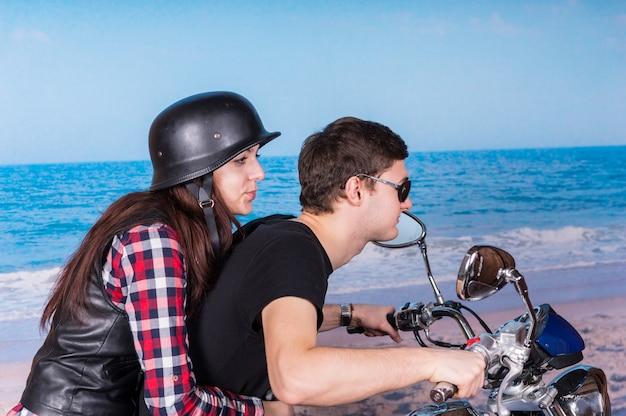 ビーチでバイクに乗ってツーアップに乗って若いカップルの縦断ビュー