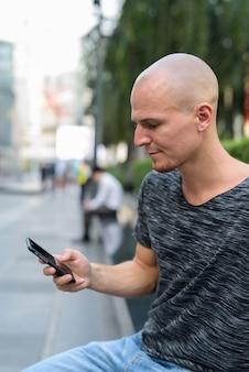 Вид профиля молодого красивого лысого мужчины с помощью мобильного телефона