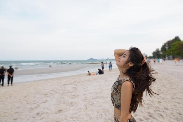 Вид профиля молодой счастливой красивой азиатской женщины улыбается