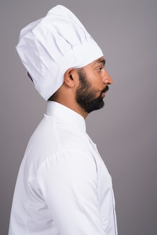 Вид профиля молодого индийского шеф-повара на сером фоне