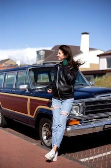 Вид профиля молодой женщины с волосами, дует ветер. на ней кожаная куртка, на заднем плане - машина и дорога.