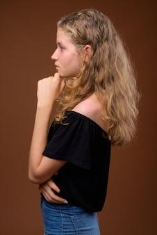 考えている若い美しい金髪の10代の少女の縦断ビューの肖像画