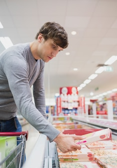 Profile view of serious man buying food