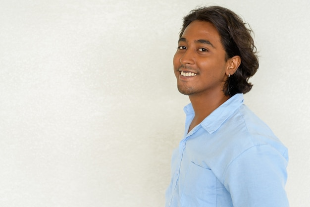 자연광으로 야외에서 촬영한 평범한 배경에 대해 잘생긴 젊은 인도 남자의 프로필 보기 샷