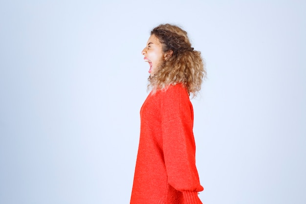 Profile view of a shouting woman in red shirt.