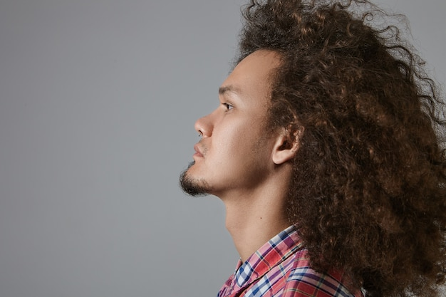 Profile view of stylish serious young mixed race bearded male with curly hairdo dressed in checkered shirt