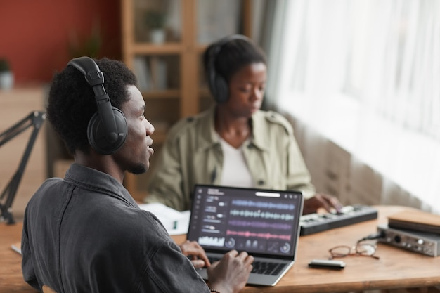 Profile view at young african-american musician wearing headphones while composing music at home recording studio, copy space