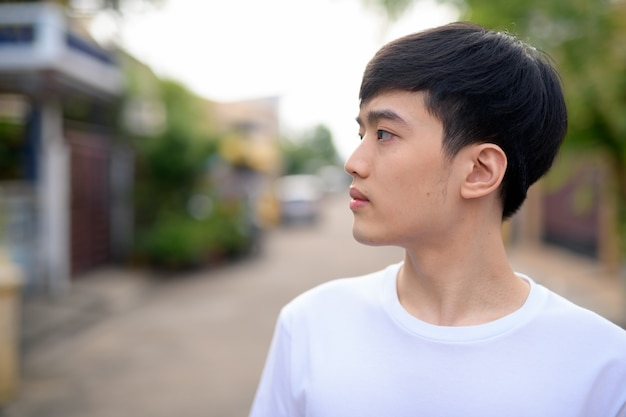 Profile view of young asian man thinking in the street