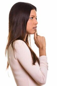 Profile view of young beautiful brazilian woman thinking