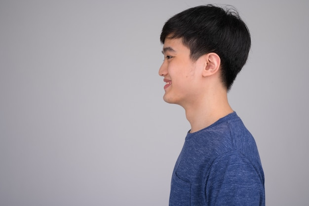 Profile view of young happy asian man smiling