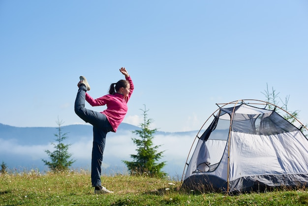 Profile view of young slim tourist girl standing on one leg in yoga pose on green grassy valley at tourist tent under beautiful blue sky on foggy mountains