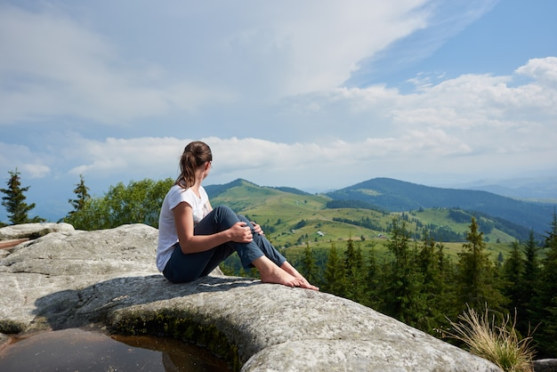 Profile view of young tourist girl sitting on huge rock with big puddle