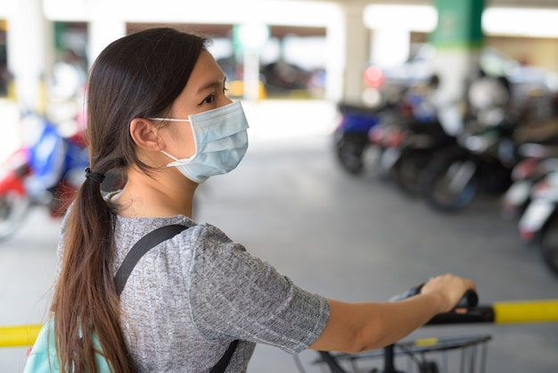 Profile view of young woman with mask holding bicycle