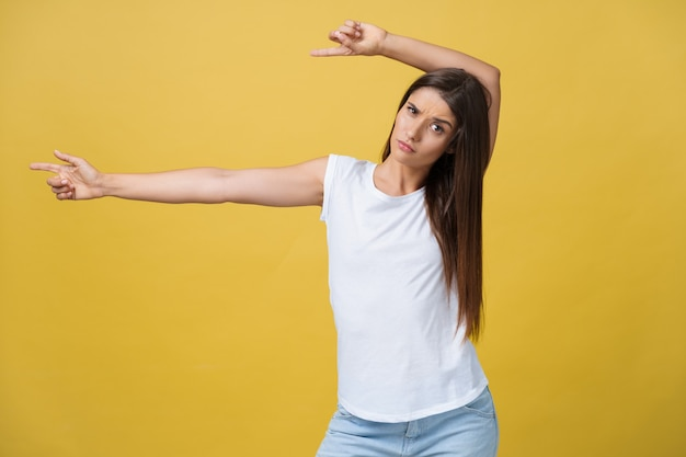 Profile of a woman pointing on copy space for an advertisement isolated on a yellow background