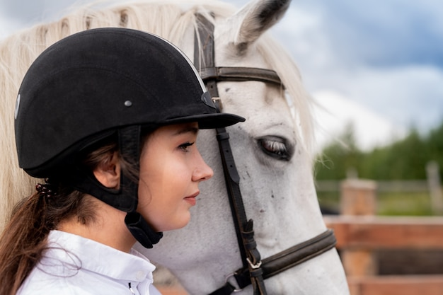 Profile of young active woman in equestrian helmet and white purebred horse standing in natural environment
