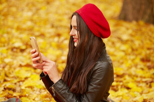 Profile of young attractive cute girl dresses red beret and leather jacket, holding smart phone in front of her