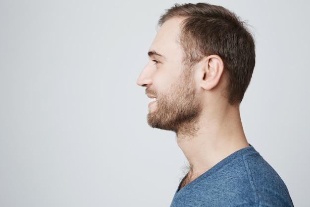 Profilo di giovane uomo barbuto che sorride, guardando a sinistra
