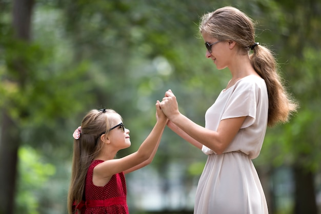 Profile of young blond long-haired attractive smiling woman and small child girl in sunglasses and fashionable dresses holding hands looking on each other on sunny summer green bokeh .