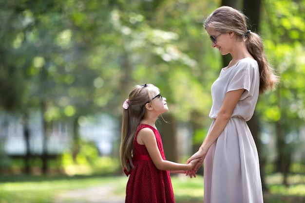 Profile of young blond long-haired attractive smiling woman and small child girl in sunglasses and fashionable dresses holding hands