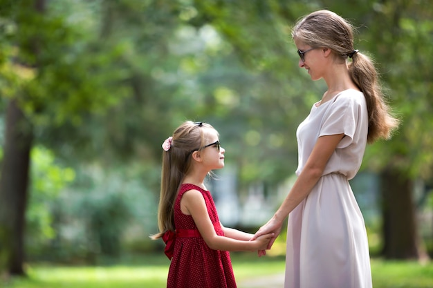Profile of young blond long-haired attractive smiling woman and small child girl in sunglasses and fashionable dresses.