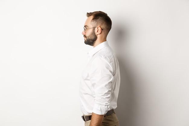 Profilo di giovane uomo d'affari in camicia di colletto bianco e pantaloni beige, guardando a sinistra, in piedi su sfondo di studio.