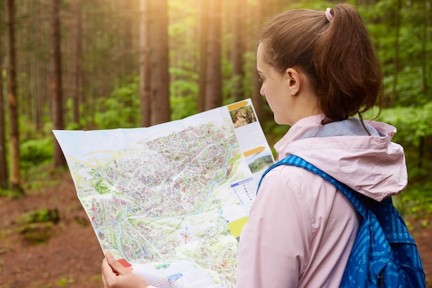 Profile of young caucasian female with blue backpacks and map being in wood, hiker looking at map and try to find way