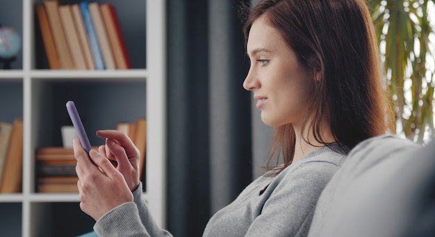 Profile of young dark-haired woman using cellphone sitting on sofa at home