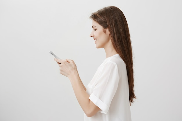 Profile of young pretty woman texting, using mobile phone, order online