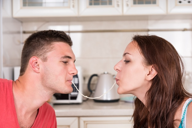 Profile of young romantic couple at dinner time sharing single strand of spaghetti, slurping together until they kiss