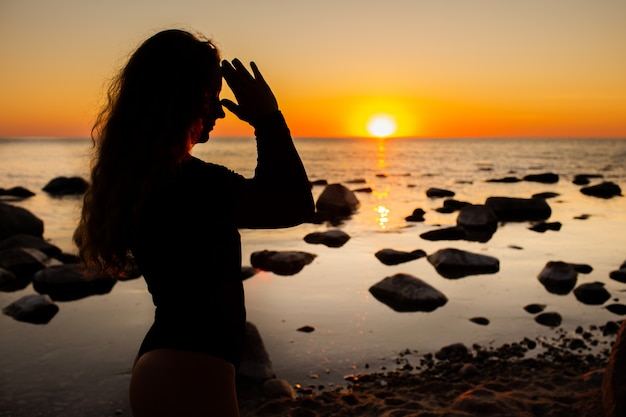 Profile of young woman relaxing on the beach, meditating with hands in namaste gesture at sunset or sunrise, close up, silhouette.
