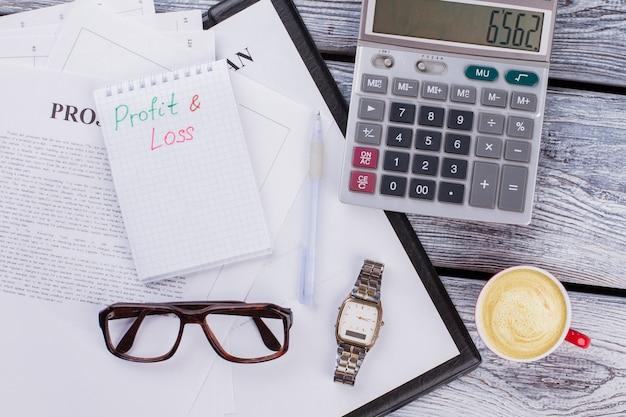 이익과 손실 개념입니다. 흰색 나무 테이블에 금융 및 비즈니스 서류입니다.