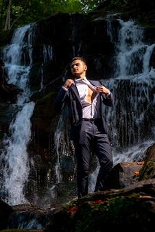 利益ビジネスコンセプト。泳ぐ準備ができている滝で脱いでいるビジネスマン。素晴らしい金融の滝。富と成功。