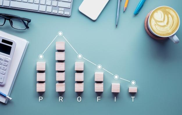 Падение прибыли, убытки с графиком вниз на столе, успех бизнеса и результат дохода