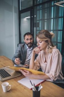 収益性の高い契約。書類を見て若い気配りのビジネス女性とスーツを着た大人の男性がオフィスの机に座って説得力のある話