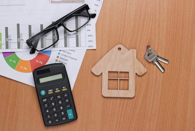 Выгодное вложение. анализ рынка. покупка недвижимости. дом minifigure, графики и диаграммы, калькулятор на столе. вид сверху