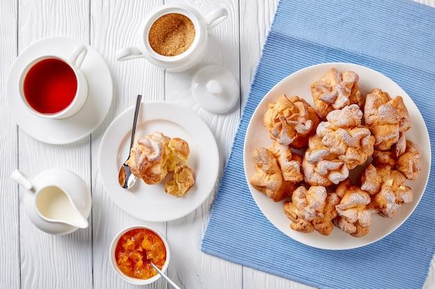 Профитроль или эклер. профитроль с начинкой из взбитых сливок подается на белой тарелке с чаем и абрикосовым джемом в миске на деревянном столе, горизонтальный вид сверху, плоский
