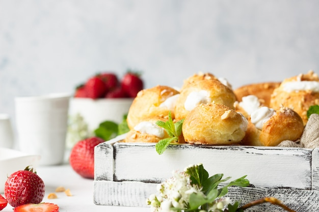 Profiteroles (choux à la crème) - french choux pastry balls with cottage cheese and cream with strawberry, mint and cup of coffee.