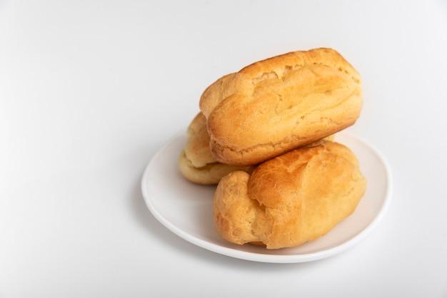 Профитроли или эклеры без сливок на белом блюдце. белая поверхность. домашняя выпечка.