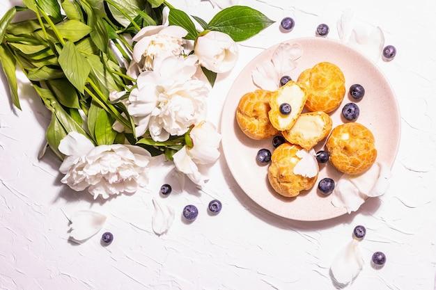 ブルーベリーとプロフィットロール。カスタードケーキ、エクレア、シュークリーム。モダンなハードライト、ダークシャドウ。しっくいの背景、上面図に白い牡丹