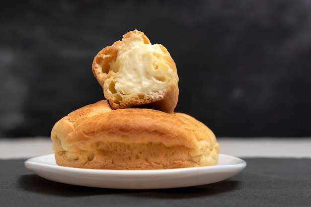 Profiteroles with curd filling. homemade baking. dessert eclairs on black background. close up