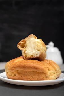 Профитроли с творожной начинкой. домашняя выпечка к чаю. десертные эклеры на черном фоне. закройте вверх.