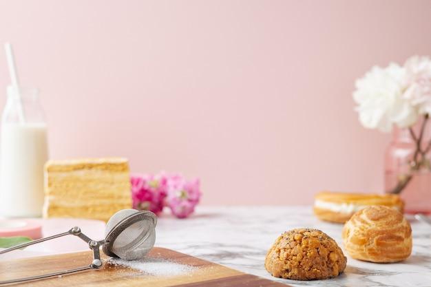 カスタードのプロフィットロール、大理石のテーブルの上のおいしいケーキ。甘いデザートの側面図。ピンクのテキスト用のスペース
