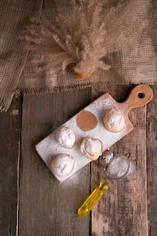 Profiteroles with icing sugar on wooden background. rustic style.