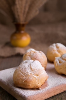 Profiteroles with powdered sugar on wooden background. rustic style. close up.